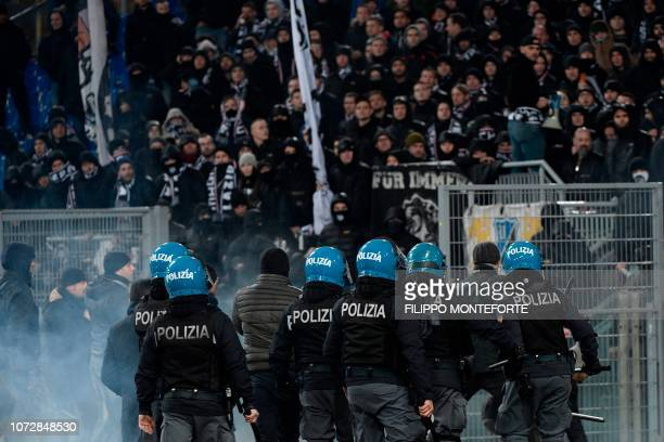 TOPSHOT Italian antiriot policemen stand guard by the curve of Eintracht Frankfurt's fans during the UEFA Europa League group H football match Lazio...