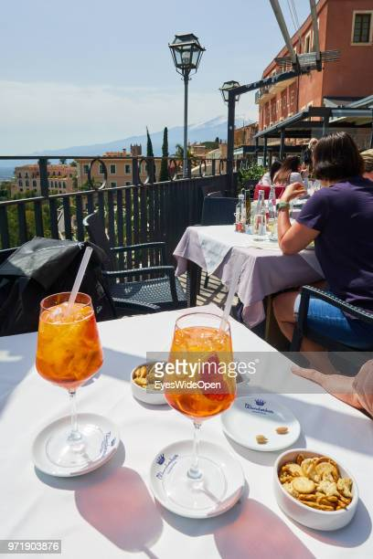 Italian Aperitif two glasses of Aperol Sprizz and snacks at the terrace of a sunny cafe in the historic center on April 8 2018 in Taormina Sicily...
