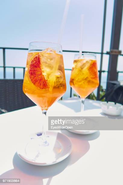Italian Aperitif two glasses of Aperol Sprizz drink at the terrace of a sunny cafe in the historic center on April 8 2018 in Taormina Sicily Italy