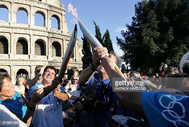 Italian archer Ilario Di Buo gives the Olympic flame to Italian Judoka Emanuela Pierantozzi in front of Rome's Coliseum, 28 June 2004 during the...
