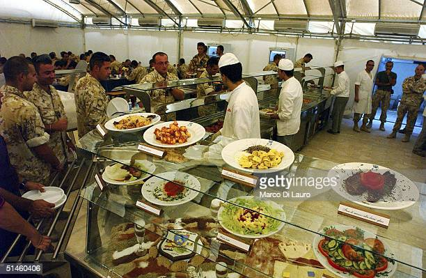 Italian Army chefs from the Italian Joint Task Force Iraq, Brigata Friuli serve food to the soldiers at the dinning hall at their base, Camp Mittica...