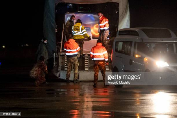 Italian Army officers load doses of Pfizer-BioNTech Covid-19 vaccine on a military plane at the military airport Pratica di Mare, on December 26,...