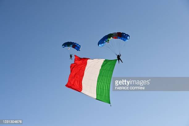 Italian Army paratroopers descend with the Italian national flag, on February 21, 2021 during the closing ceremony of the FIS Alpine World Ski...