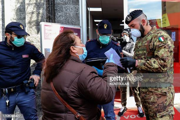 Italian Army soldiers and police check that a citizen has self-certification to be able to circulate in this period of limitation of movement of...