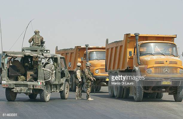Italian Army soldiers from the Italian Joint Task Force Iraq, Friuli Brigade, check vehicles at a permanent check point on the Tampa road from Basrah...