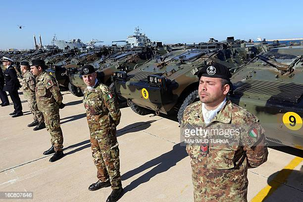 Italian Army soldiers stand by some of the twenty military vehicles during an handing over ceremony by Italy to Libya at a Libyan Navy Base on...