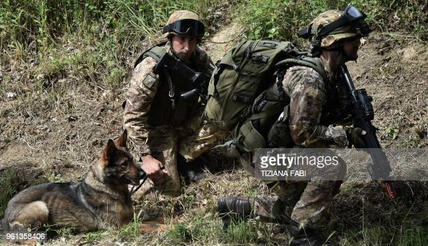 Italian Army soldiers take part in a military exercise with an army dog at a training camp in Cesano near Rome on May 21 2018