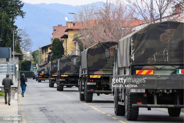 Italian Army trucks transporting coffins of victims of coronavirus cross the city of Bergamo, Lombardy, after leaving the Monumental Cemetery on...