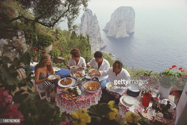 Italian artist and actress Domiziana Giordano Italian author Francesca Sanvitale Dino Trappetti and Umberto Terrelli dining al fresco on a terrace...