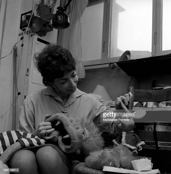 Italian artist and puppet maker at work and joking with Topo Gigio one of her puppets Milan 1960s