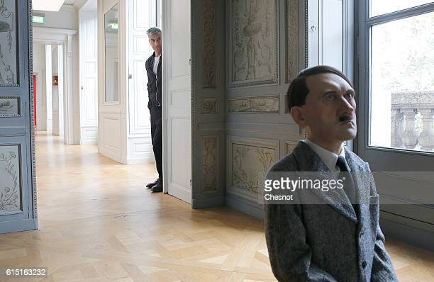 Italian artist Maurizio Cattelan poses next to his artwork 'Him' depicting Hitler on his knees in prayer prior to the opening of the exhibition Not...