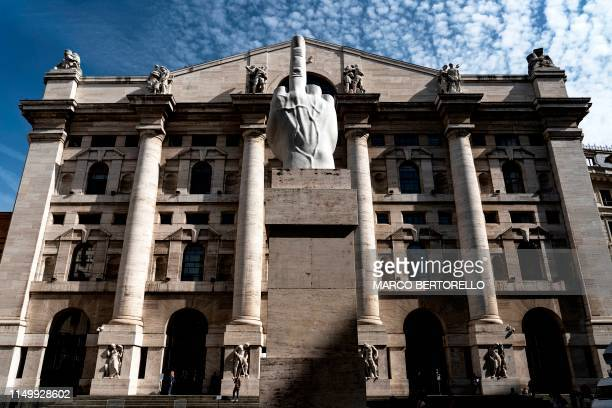 TOPSHOT Italian artist Maurizio Cattelan's sculpture LOVE displayed in front of the Palazzo Mezzanotte Italy's stock exchange building is pictured on...