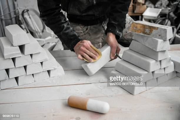 Italian artist Nazareno Biondo sculpts marble's ingots in his workshop on May 16 2018 in Cafasse near Turin Biondo his actually working on a replica...