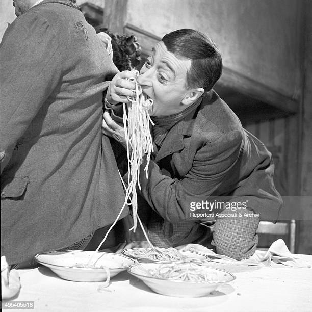 Italian artist Totಠeating spaghettis in a scene from the film Poverty and Nobility Rome 1954
