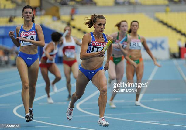 Italian athlete Chiara Bazzoni hands the baton to teammate Maria Enrica Spacca as they compete in the women's 4x400 metres relay heats at the...