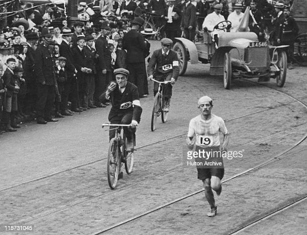 Italian athlete Dorando Pietri approaches the White City Stadium at the end of the marathon, during the 1908 Summer Olympics in London, 24th July...