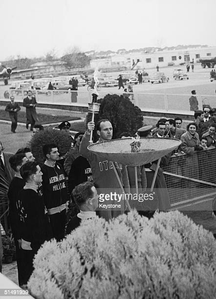 Italian athlete Giuseppe Dordone lights the olympic flame at Ciampino Airport, Rome, 22nd January 1956. Dordone is due to take the flame to Cortina...