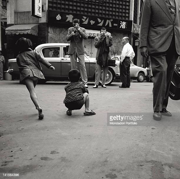 Italian athletes filming a Japanese child on a street with two video cameras during the Tokyo Olympics Japan October 1964