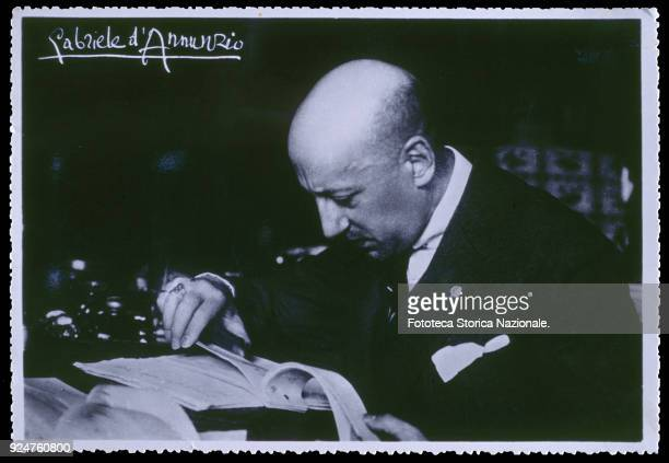 Italian author Gabriele D'Annunzio at his desk in his studio at the Vittoriale Photographic postcard with autograph Italy Gardone Riviera Brescia 1920