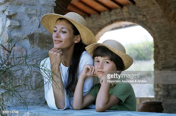 Italian ballet dancer Carla Fracci and her son Francesco wearing straw hats 1978