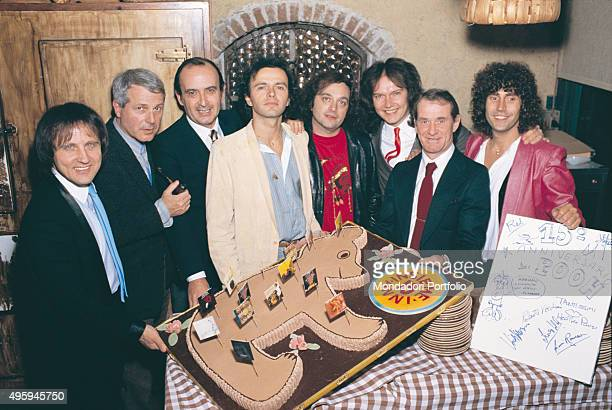 Italian band Pooh posing around a big cake in the shape of WinniethePooh in company with two CGD managers a lyrics author and the CGD graphic manager...