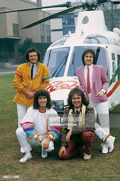 Italian band Pooh posing smiling beside the helicopter standing on the playground of a stadium where they will perform in the summer Clockwise from...