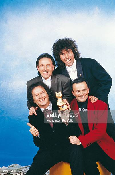 Italian band Pooh posing with a Telegatto during a photo shoot From top left Roby Facchinetti Stefano D'Orazio Dodi Battaglia and Red Canzian Italy...