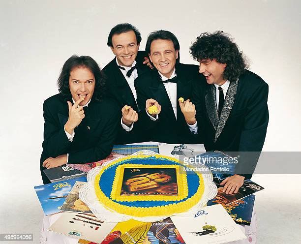 Italian band Pooh smiling around a big cake with the cover of their double album 'Pooh 25 - La nostra storia' in the middle. Photo shoot realized on...