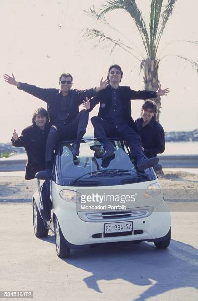 Italian band 'Stadio' posing on the seafront on a Smart car From the left the guitarist Andrea Fornili the drummer Giovanni Pezzoli the singer and...