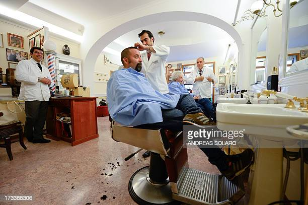 Italian barber Alessandro Migliacci and his father Piero cut customers' hair in their famous barber shop in central Rome 'Antica Barbieria Peppino...