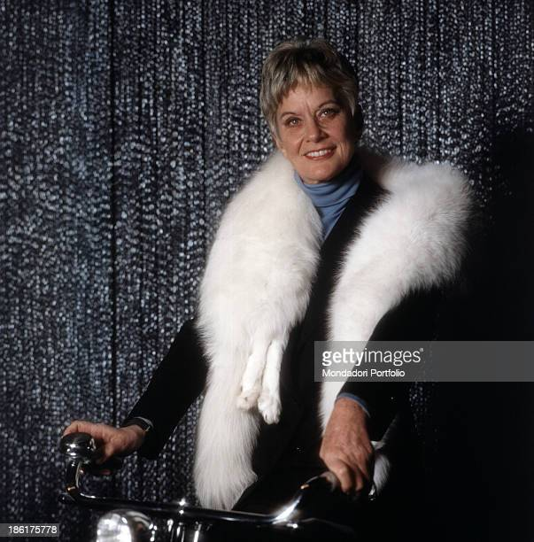 Italian baroness and singer Alida Valli sitting on the saddle of a bicycle and wearing a white fox fur scarf 1981