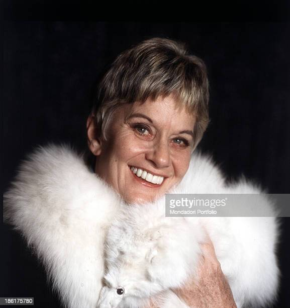Italian baroness and singer Alida Valli smiling and wrapping around her neck a white fox fur scarf 1981