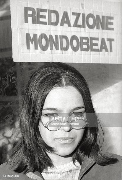 Italian beatnik standing under a sign of 'Mondo Beat' magazine 1960s