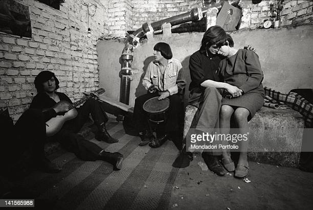 Italian beatniks hugging and playing at Mondo Beat club in Milan Milan 1960s