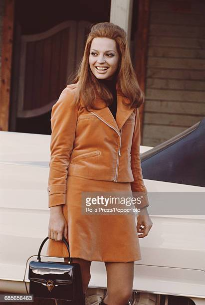 Italian born actress Ira von Furstenberg pictured wearing a matching orange velvet jacket and skirt suit during production of the comedy film...