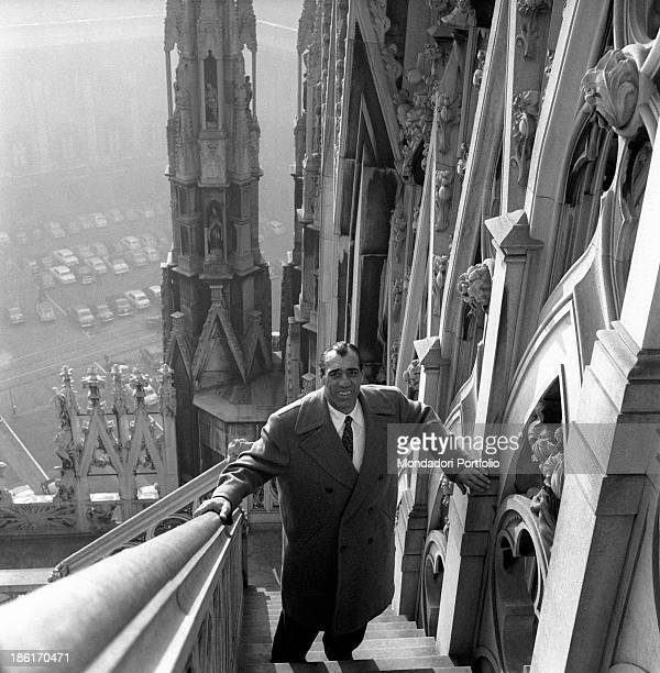 Italian boxer and actor Primo Carnera posing on a staircase on the terraces of the Duomo Behind him the façade of Palazzo Reale and some parked cars...