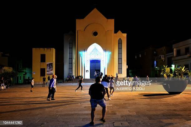 Italian boys and young migrants play a football match on the square of the parish of San Geraldo in Lampedusa on September 26 2018 Five years after...