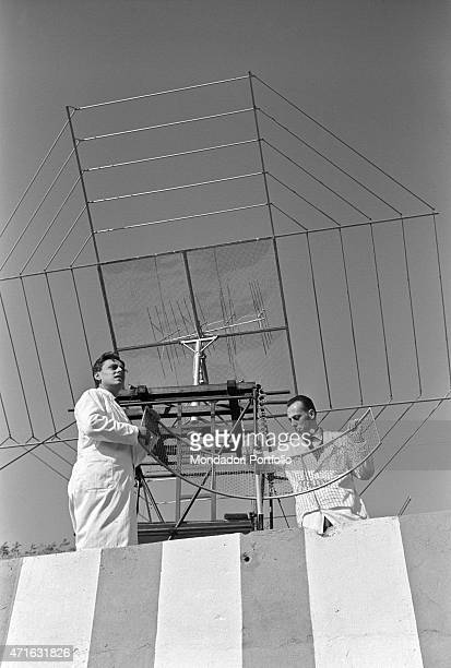 'Italian brothers and radio amateurs Achille and Giovanni Battista Judica Cordiglia settling an antenna to listen to Soviet and American astronauts'...