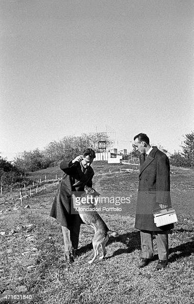 'Italian brothers and radio amateurs Achille and Giovanni Battista Judica Cordiglia playing with a dog in front of Bert Tower their space listening...
