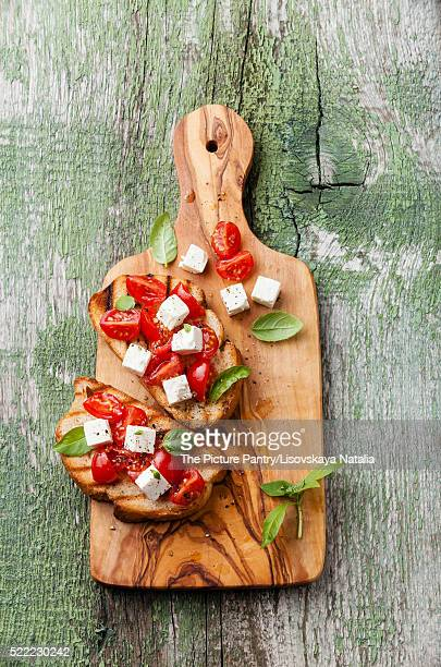 Italian bruschetta with chopped tomatoes, basil and cheese on gr