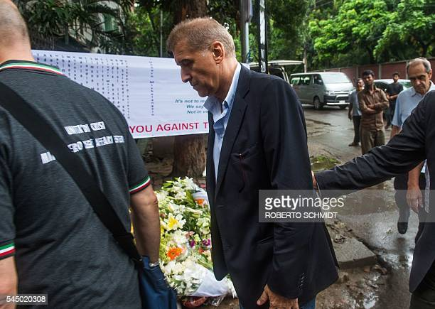 Italian businessman Gianni Boschetti walks past flower arrangements left by well wishers at a road block leading to the Holey Artisan Bakery after he...