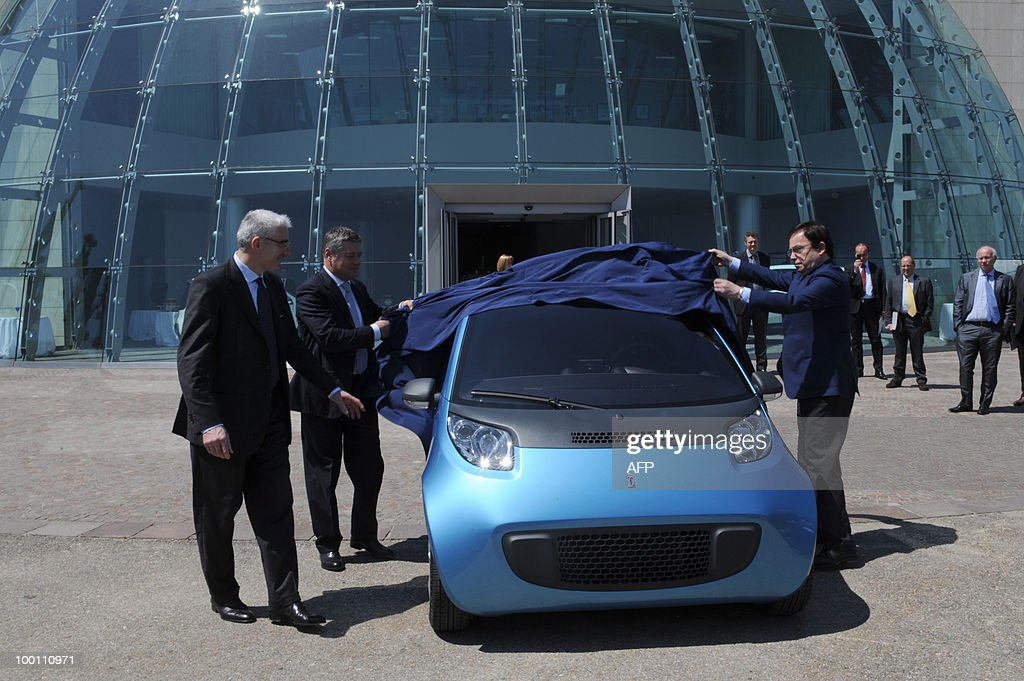 Italian car maker Pininfarina President Paolo Pininfarina (C), Pininfarina CEO Silvio Pietro Angori (L) and Italian under Secretary of Infrastructure and Transport Bartolomeo Giachino (R) unveil the new Pininfarina electric car 'Nido' during the 80th anniversary celebrations of Pininfarina group in Cambiano near Turin on May 21, 2010.