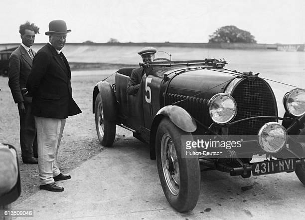 Italian car manufacturer Ettore Bugatti and another man stand next to Ettore's son Jean in a racecar before the French Grand Prix