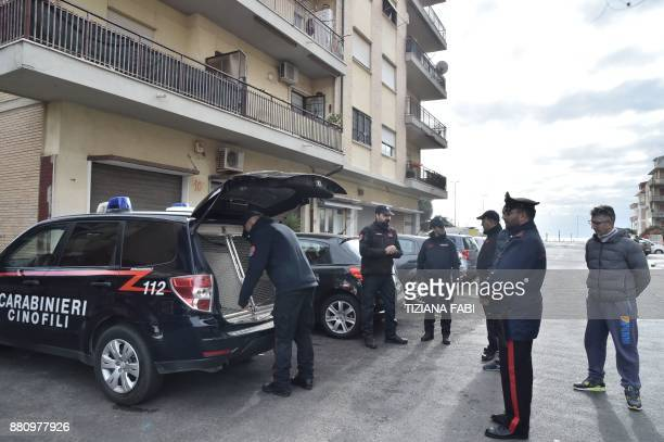 Italian carabinieri bring a sniffer dog on November 28 2017 to conduct searches in Ostia Rome's seaside district where the Spada clan lives...