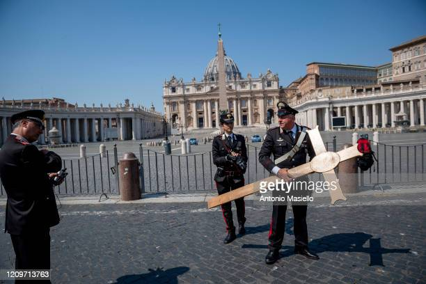 Italian Carabinieri carry a cross in the St Peter's square while Pope Francis celebrates the Easter Mass inside the empty St Peter's Basilica during...