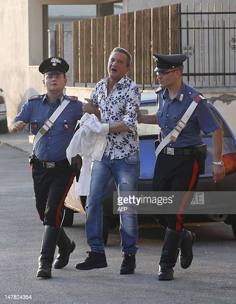 Italian Carabinieri escort Neapolitan singer Tony Marciano after being arrested during a crackdown against the Gionta clan of the powerful Naples...