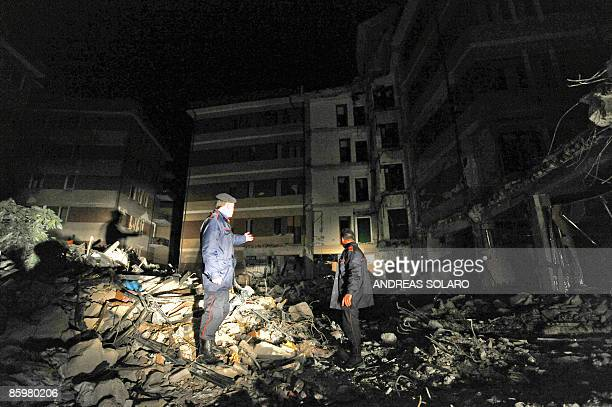 Italian Carabinieri inspect the rubble during a night patrol in front of the collapsed building housing a university students' dorm of the devastated...
