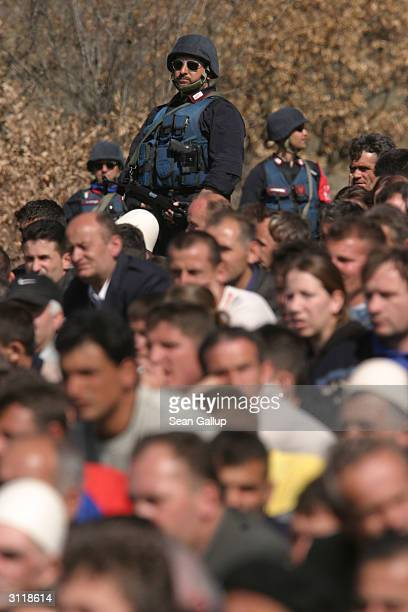 Italian Carabinieri KFOR troops keep a watchful eye as thousands of Kosovar Albanians attend the funeral of youngsters Egzon Deliu and Avni Veseli...
