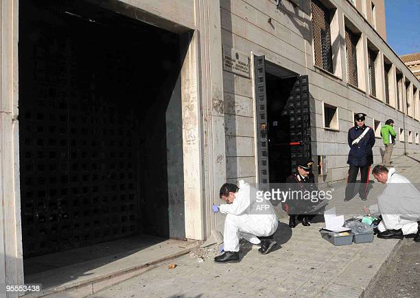Italian Carabinieri military police officers collect evidence in front of the entrance building of the Reggio Calabria's court on January 3 2010 A...