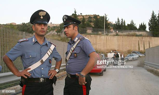 Italian Carabinieri patrol near the entrance gate to a vat in Mineo where six workers died on June 11 2008 They were cleaning in the vat at a plant...
